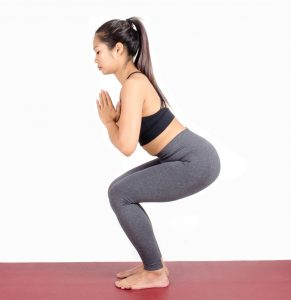 Pre-workout yoga like the Chair Pose may assist with proper weightlifting form.