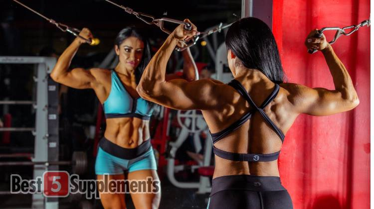 A woman showing the best supplements to help get you jacked