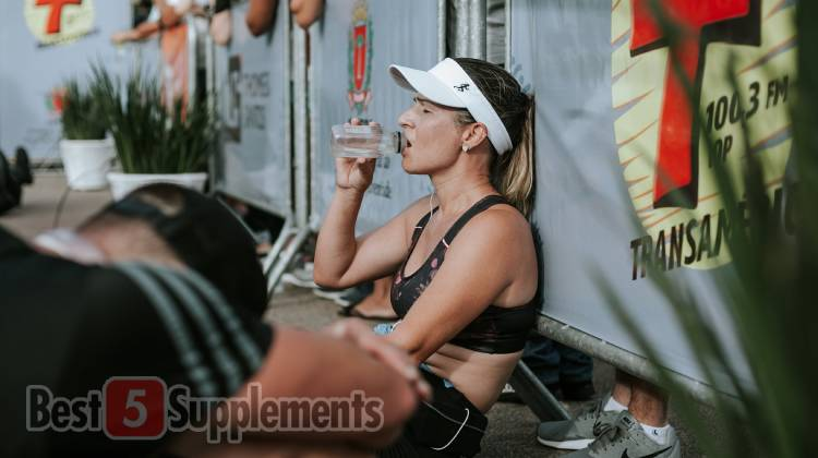 Female marathon runner looking exhausted and drinking from a bottle.