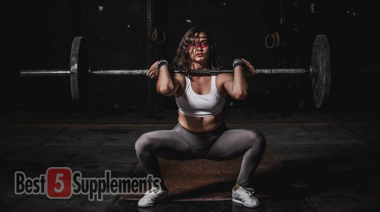 A female in a white top and grey leggings performing a front squat in the gym