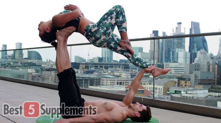 A man balancing a women while performing yoga to display the best vegan fat burner on sale