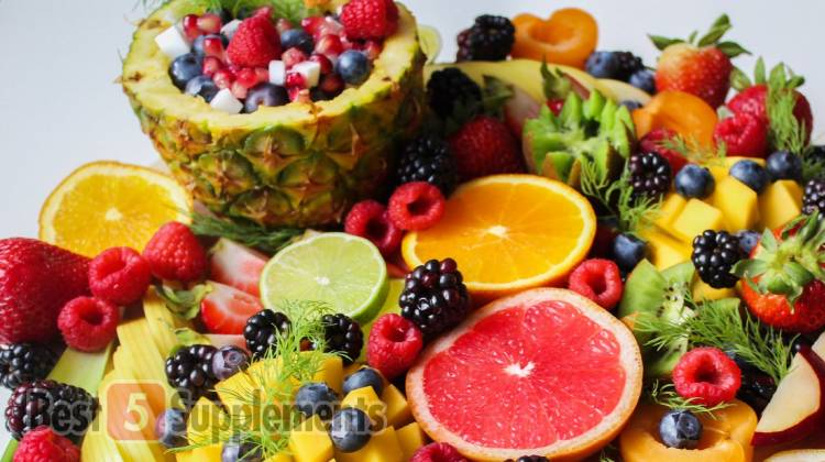 A selection of colorful fruit on a platter against a grey backdrop