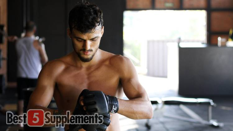 A man wrapping his boxing gloves wanting the best weight loss and recovery supplements