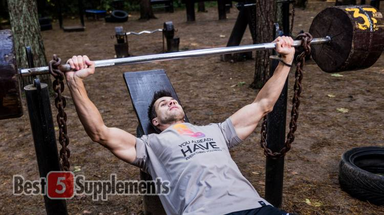 Fit man led preparing to bench press in an outdoor gym