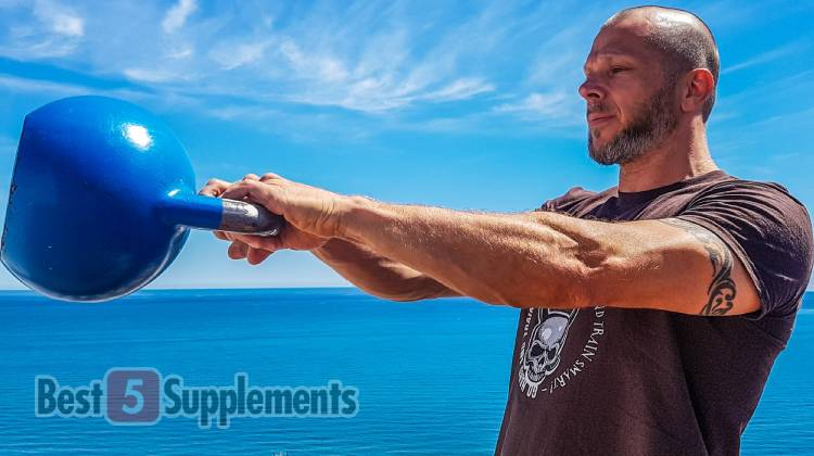 A man lifting a kettle bell with the background being an ocean and blue skies