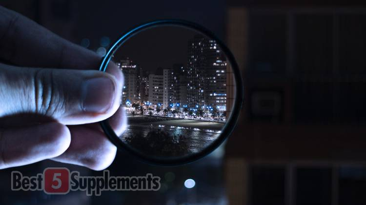 An image of fingers grasping a magnifying glass with all surrounding areas blurry