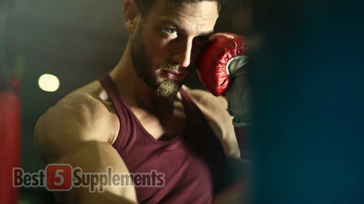 A man with a boxing glove on showing his muscular arm and half of his face