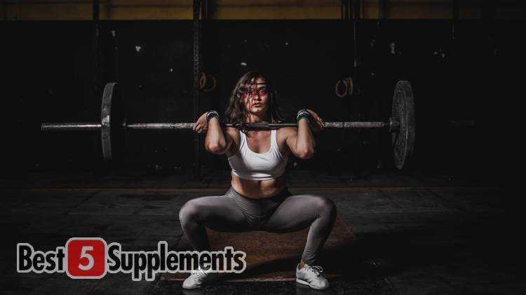 A female performing a clean and press with a barbell, in front of a dark background of a gym